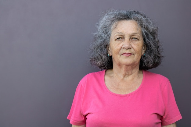 Una donna anziana con i capelli grigi in una maglietta luminosa su uno sfondo grigio guarda la telecamera. donna matura in abiti rosa con lentiggini sul viso. ritratto integrale. nonna da vicino Foto Premium