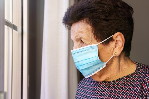 Donna anziana con una maschera dentro casa che guarda fuori dalla finestra con paura dell'esterno, a causa del coronavirus covid-19.