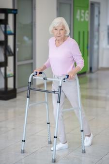 Donna anziana con un deambulatore che va nel corridoio