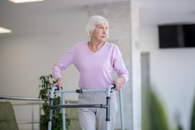 Donna anziana con un deambulatore che osserva da parte