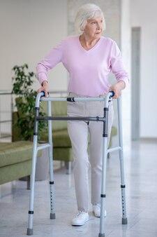Donna anziana con un deambulatore che sembra serio