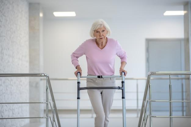 Donna anziana con un deambulatore che sembra stanco