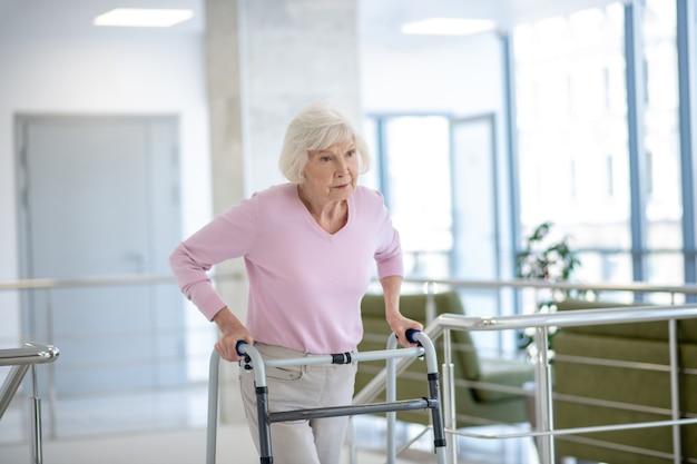 Donna anziana con un deambulatore che sembra infelice