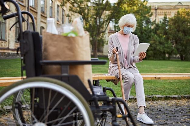 Donna anziana con un bastone da passeggio seduto su una panchina e guardando lo schermo di un tablet. sedia a rotelle al suo fianco