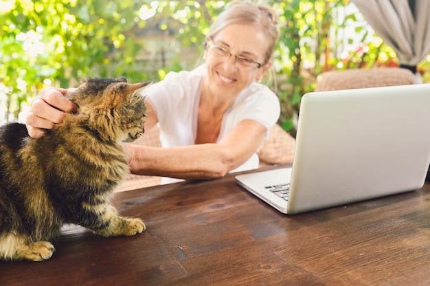 Donna anziana che lavora su un computer portatile