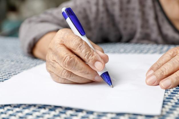 Donna anziana che scrive su carta bianca
