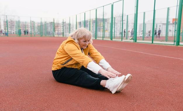 Una donna anziana con una giacca gialla sta facendo esercizi sportivi su un tapis roulant rosso. lo stadio è uno stile di vita sano. pensionati e sport. donna anziana attiva
