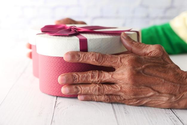 Donne anziane in possesso di una confezione regalo a forma di cuore