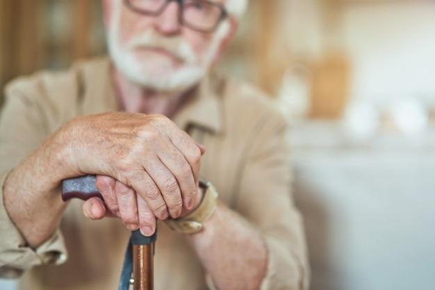 Mani maschili rugose anziane sul bastone da passeggio