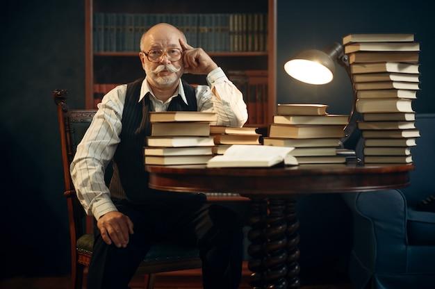Scrittore anziano seduto al tavolo con una pila di libri in ufficio a casa. il vecchio con gli occhiali scrive un romanzo di letteratura in una stanza con fumo, ispirazione