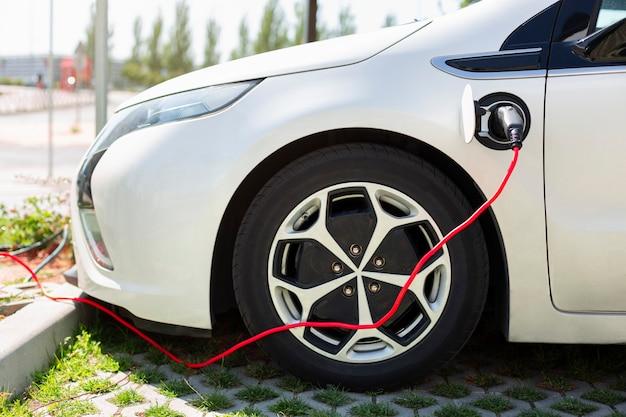 Ricarica della batteria dell'auto elettrica. caricabatterie ecologico per veicoli ibridi. concetto di energia sostenibile e mobilità. ecologia pulita.