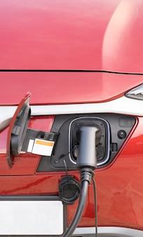 Punto di ricarica per auto elettriche per auto elettriche concetto di auto elettrica nell'ambiente verde