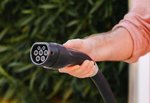 Spina per auto elettrica tenuta da una mano d'uomo con sfondo verde naturale. concetto di mobilità ecologico