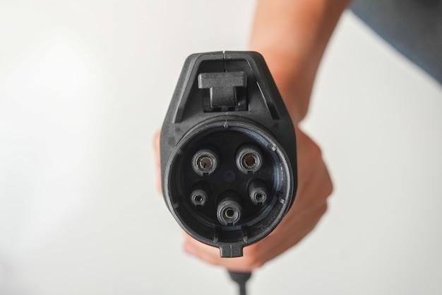 Presa per auto elettrica per la ricarica del veicolo elettrico. presa nera su sfondo bianco.