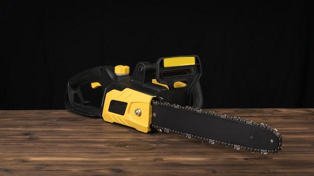 Sega a catena elettrica su un tavolo in legno marrone su sfondo nero. utensile elettrico per la lavorazione del legno.