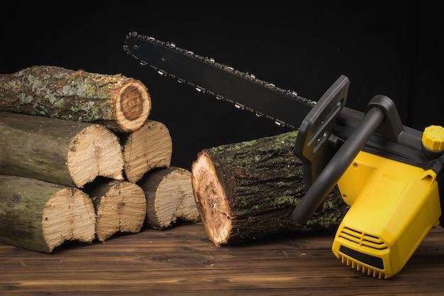 Seghe elettriche a catena seghe tronchi di legno su uno sfondo di legno. utensile elettrico per la lavorazione del legno.