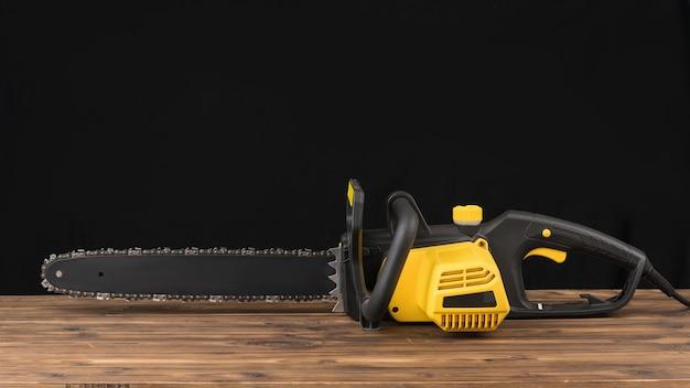 Sega a catena elettrica su un tavolo di legno su uno sfondo nero. utensile elettrico per la lavorazione del legno.