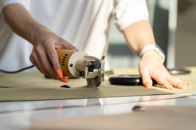 Taglierina elettrica per tagliare il primo piano tessile del lavoro manuale femminile con il tessuto nella stanza dello studio dell'atelierlier
