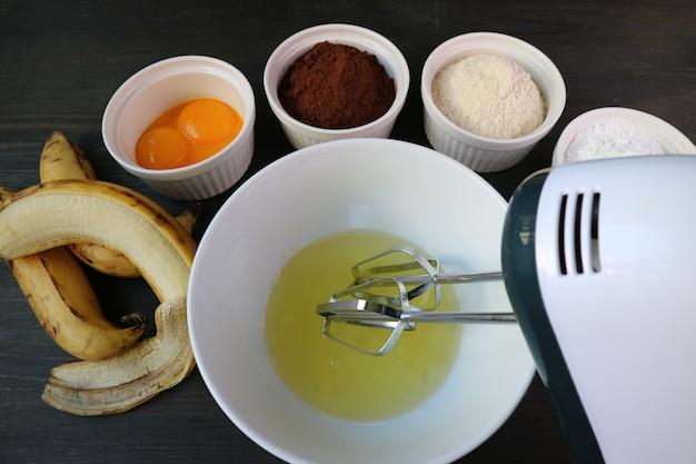 Frullino per le uova elettrico in una ciotola di albume circondato da altri ingredienti