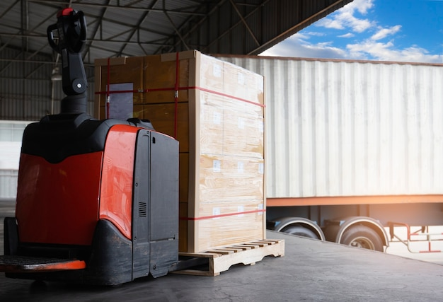 Carrello elevatore elettrico pallet jack con carico di scatole di carico con camion di rimorchio per container di carico parcheggiato carico al magazzino di banchina