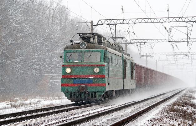 Il treno merci elettrico si sta muovendo in una tempesta di neve