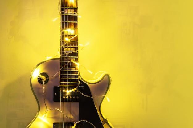 Chitarra elettrica con ghirlanda illuminata su sfondo scuro. regalo di capodanno sotto forma di costose chitarre elettriche. regalo per il musicista a natale. uno strumento musicale