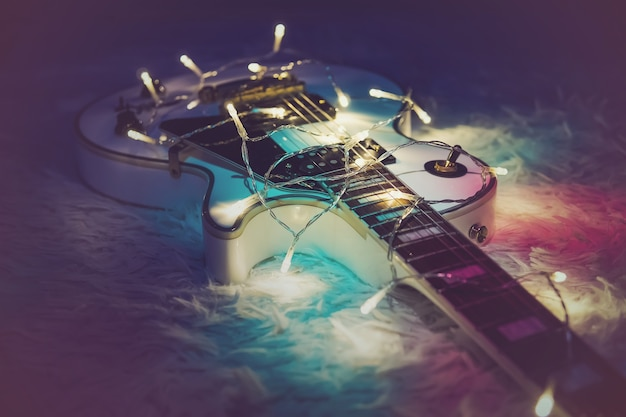 Chitarra elettrica con ghirlanda illuminata. regalo di capodanno sotto forma di costose chitarre elettriche. regalo per il musicista a natale. uno strumento musicale nei raggi delle luci splendenti.