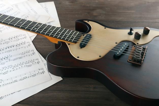 Chitarra elettrica con note musicali su tavola di legno