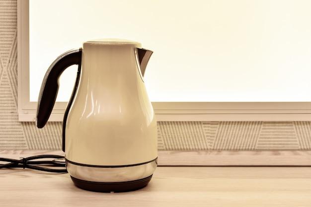 Bollitore elettrico sul tavolo della cucina sullo sfondo della finestra. elettrodomestici da cucina. finestra e bollitore