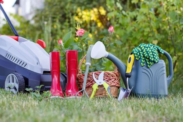 Tosaerba elettrico, stivali di gomma da giardino rossi, piccolo rastrello, potatore, cesto di vimini, cazzuola e annaffiatoio in plastica su erba verde con sfondo verde sfocato
