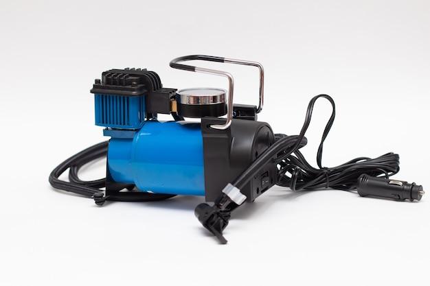La pompa elettrica si gonfia per la ruota di un'auto. compressore d'aria per auto auto isolato su sfondo bianco