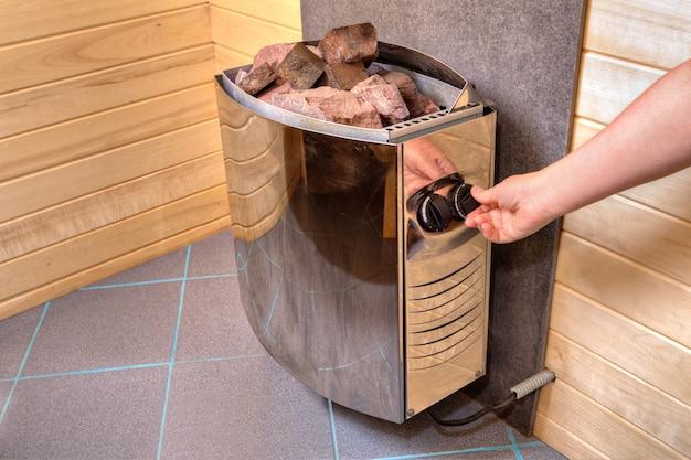 Stufa elettrica per sauna con pietre poste sopra, mano gira il regolatore sul pannello di controllo, impostazione di tempo e temperatura.