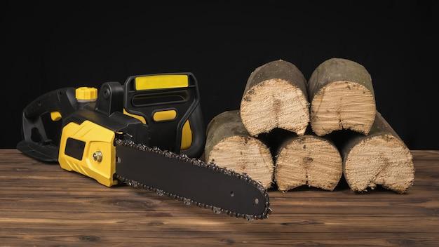 Sega elettrica su uno sfondo di legno vicino agli alberi segati. utensile elettrico per la lavorazione del legno.