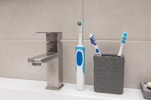 Uno spazzolino elettrico e un vecchio spazzolino da denti vicino al lavandino.