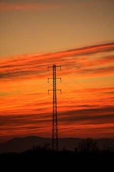Torri elettriche retroilluminate in un tramonto rosso