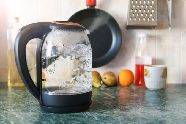 La teiera elettrica in vetro trasparente bolle in cucina Foto Premium