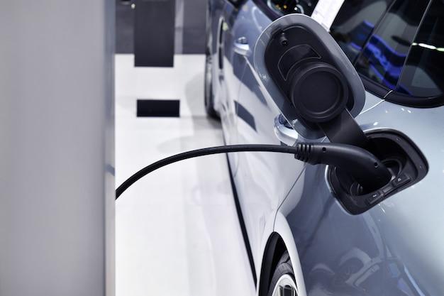 Ricarica del veicolo elettrico nella stazione con l'alimentatore collegato a un'auto elettrica in carica