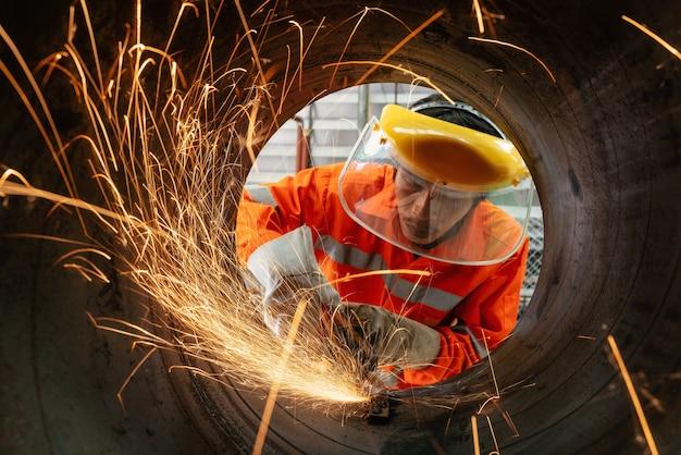 La molatura elettrica del lavoratore industriale indossa una maschera di sicurezza che taglia un tubo metallico con molte scintille taglienti