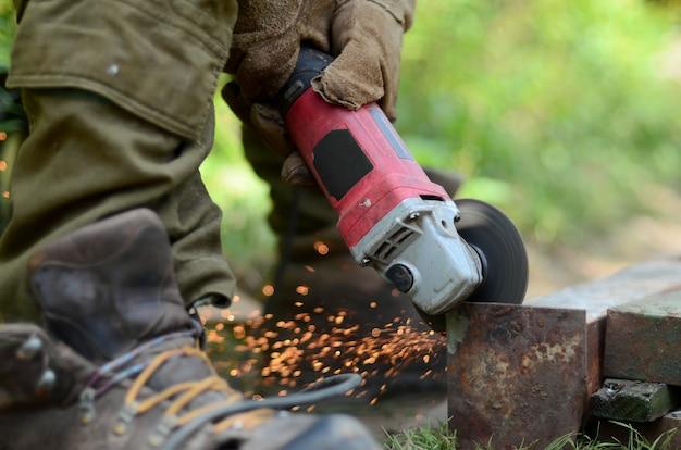 Macinazione di mole elettriche su struttura in acciaio all'aperto. operaio anziano in guanti protettivi che tagliano la porta del metallo con la smerigliatrice