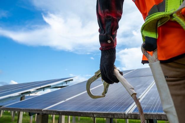 Ingegnere elettrico o tecnico di manutenzione del sistema elettrico che lavora su apparecchiature di controllo e manutenzione presso la centrale solare, concetto di energia alternativa pulita e verde.