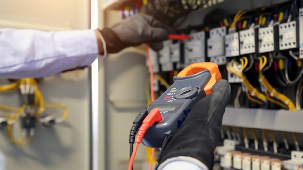 Ingegnere elettrico che utilizza apparecchiature di misurazione per controllare la tensione della corrente elettrica all'interruttore.
