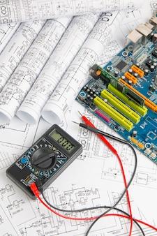Disegni di ingegneria elettrica, scheda madre del computer e multimetro digitale