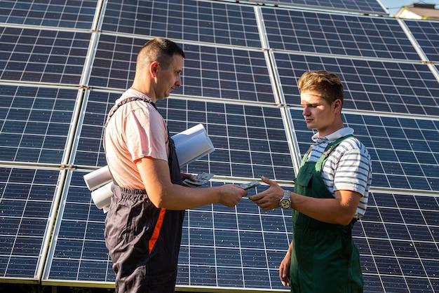 Ingegneri elettrici che esaminano la costruzione vicino a batterie a energia solare, energia verde