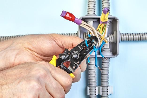 Servizi di installazione elettrica, l'elettricista utilizza spelafili per rimuovere l'isolamento