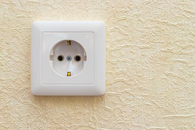 Una presa elettrica a parete in ufficio o in appartamento. sfondo giallo.