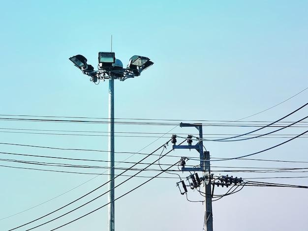 Posta elettrica e linee elettriche contro il cielo blu chiaro