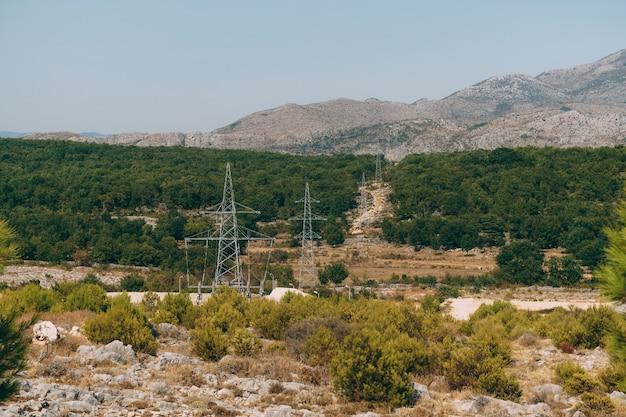 Piloni elettrici delle linee elettriche nella foresta contro la superficie delle montagne