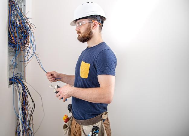 Elettricista al lavoro, esamina il collegamento del cavo nella linea elettrica nella fusoliera di un quadro industriale. professionista in tuta con attrezzo da elettricista.