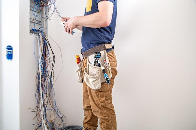 Elettricista al lavoro, esamina il collegamento del cavo nella linea elettrica nella fusoliera di un quadro industriale.