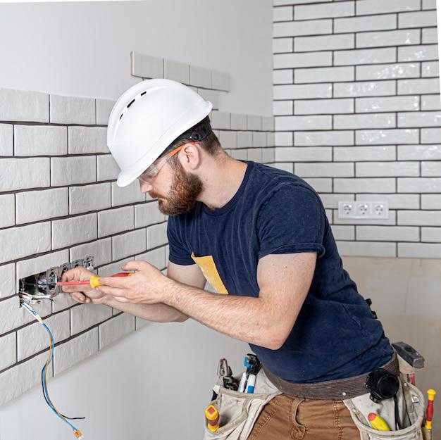 Operaio edile elettricista con la barba in tuta durante l'installazione delle prese. concetto di ristrutturazione della casa.